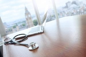 NHS - stethoscope and laptop computer on wood table and london bigben blurred background copy space