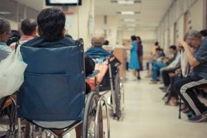 Budget cuts - Patient elderly on wheelchair and many patient waiting a doctor and nurse in hospital