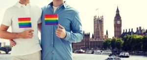 people, homosexuality, same-sex marriage, travel and love concept - close up of male gay couple holding rainbow flags and hugging from back over big ben and houses of parliament in london background