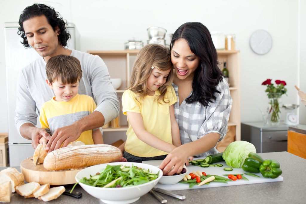 Take hold of your health - Positive family preparing lunch together in the kitchen